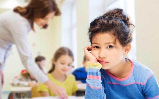 Kinder in einer Schulklasse, im Hintergrund eine Lehrerin die mit einem Kind spricht.